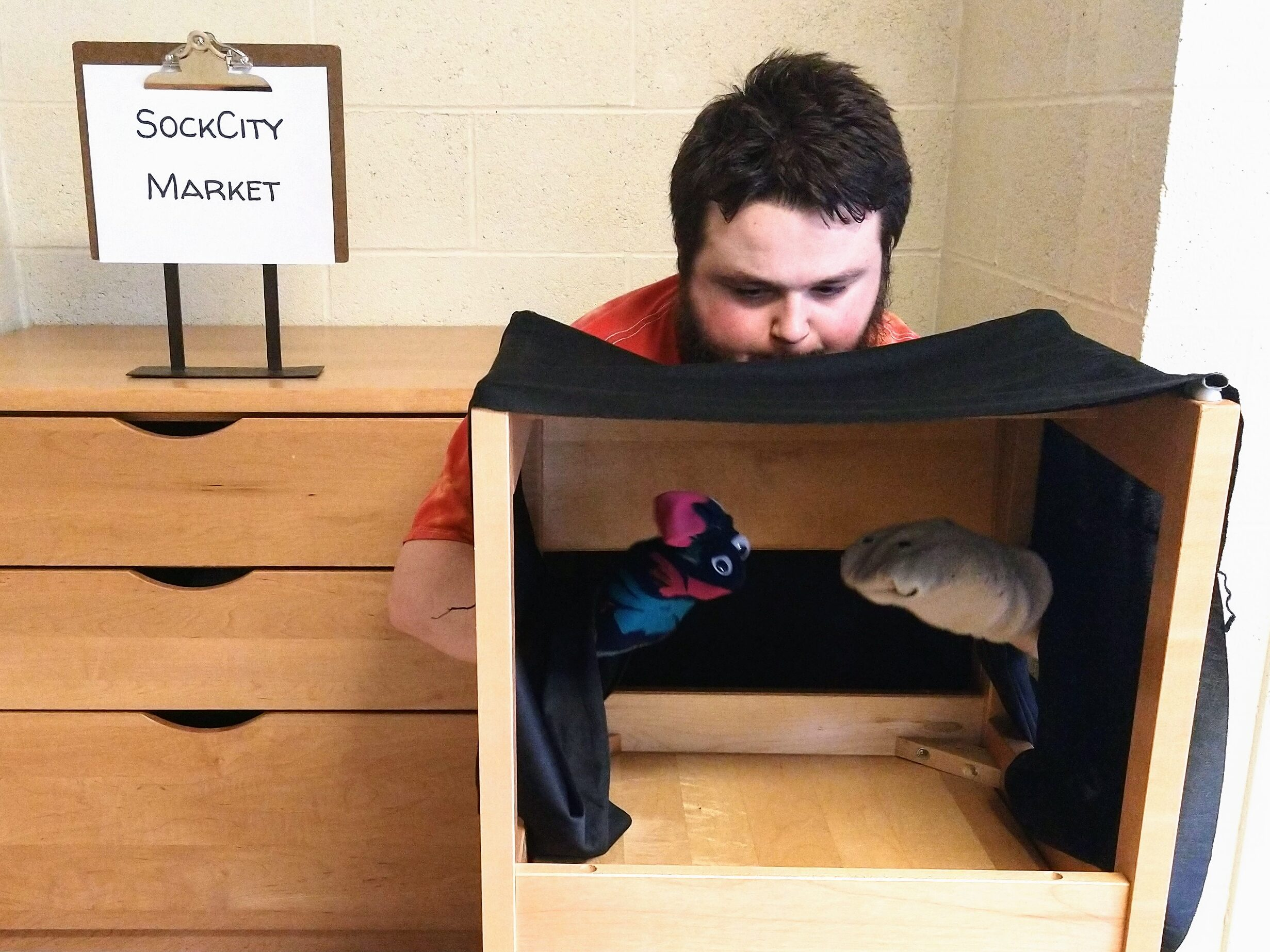 """Man holds up Chausette and Hanes in the puppet theatre. The sign behind him says """"SockCity Market"""""""